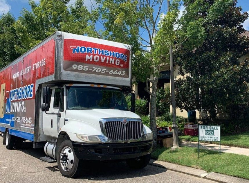 Moving truck parked outside a house for sale