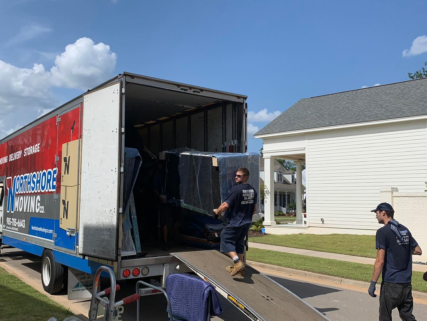 threee movers unloading furniture from moving truck