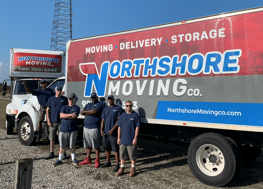 five professional movers standing in front of moving truck