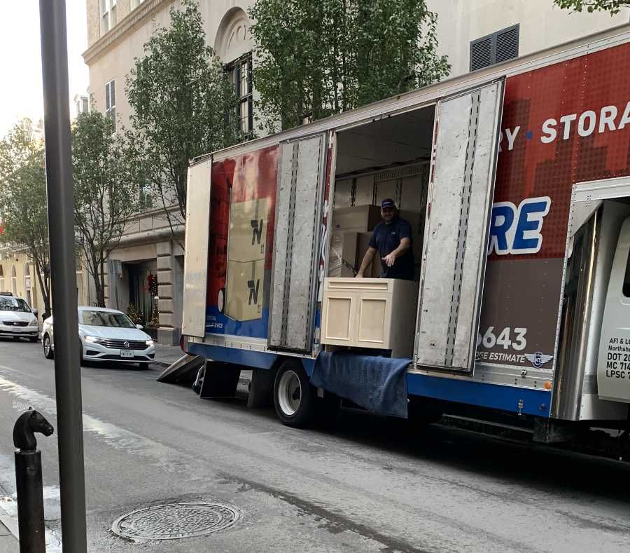 moving truck unloading furniture parked on a commercial street